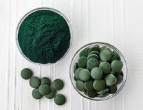 Spirulina algae powder and tablets. On white wooden background from top view Stock Image