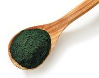 Spirulina algae powder. Wooden spoon of spirulina algae powder isolated on white background Royalty Free Stock Photo