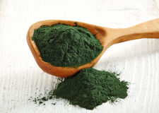 Spirulina algae powder. Wooden spoon of spirulina algae powder on white wooden background Royalty Free Stock Photos