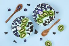 Spirulina azul y Berry Smoothie Bowl con los arándanos kiwi y chocolate imagen de archivo