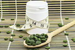 Free Spirulina,chlorella Pills On Wood Spoon And Measure Tape Around Pill Bottle Royalty Free Stock Photos - 84335578