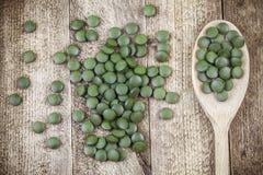 Spirulina, comprimidos do suplemento ao chlorella na colher de madeira na tabela Imagem de Stock Royalty Free