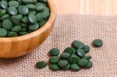 Spirulina dos comprimidos e fim verdes da alga do chlorella acima no de madeira Fotos de Stock