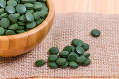 Spirulina dos comprimidos e fim verdes da alga do chlorella acima no de madeira imagem de stock royalty free