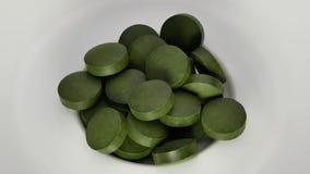 Spirulina, pillole di supplemento della clorella su bianco Fuoco selettivo video d archivio