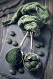 Spirulina pills and powder. Spoons with spirulina pills and powder Stock Image