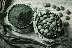 Spirulina pills and powder. Spirulina tablets and powder in bowls on a wooden background Stock Photography