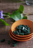 Spirulina pills on a rustic table Royalty Free Stock Image