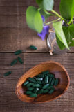 Spirulina pills on a rustic table Royalty Free Stock Photos