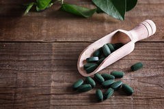 Spirulina pills on a rustic table. Spirulina pills in a scoop over wooden rustic background with copy space Stock Photo