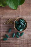 Spirulina pills on a rustic table Royalty Free Stock Photography