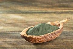 Spirulina powder dietary supplement - Text space. Spirulina powder dietary supplement - Wood background stock image