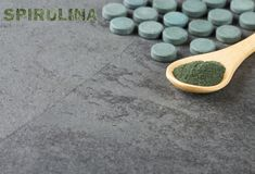 Dietary supplement of spirulina powder - Wooden spoons royalty free stock photo