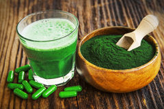 Spirulina powder and smoothie. Spirulina smoothie, powder and pills on wooden background Royalty Free Stock Photo
