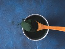 Spirulina powder in spoon on blue background Stock Photos