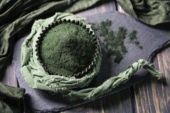 Spirulina powder. On a wooden background Stock Images