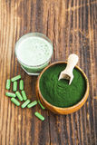 Spirulina powder in wooden bowl with spirulina pills and green s Royalty Free Stock Image