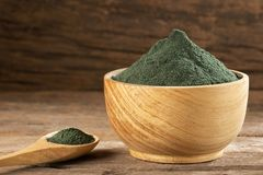 Spirulina powder in the wooden bowl. Text space. Spirulina powder in the wooden bowl royalty free stock photography