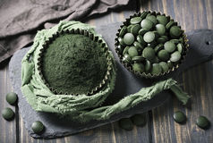Spirulina tablets and powder. In bowls on a wooden background stock image