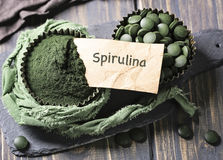 Spirulina tablets and powder. In bowls on a wooden background Stock Images