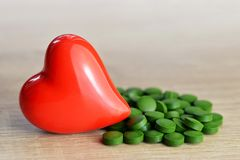 Spirulina tablets with red heart. Stock Images