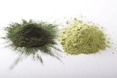 """Spirulina y el polvo crudo de la hierba de cebada en el †blanco del fondo """"apilan Fotografía de archivo"""