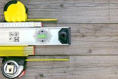 Spirytusowy poziom z taśmy miarą i falcowanie regułą na szarym drewnianym b fotografia stock