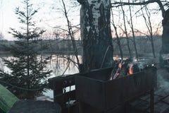Spis med bränningvedträ nära björkträdet och det härliga dammet, utomhus- helg arkivfoto
