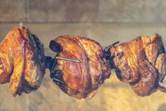 A spit for cooking roast shank in Prague on a Sunny day. A big piece of meat. National cuisine. Appetizing grilled pork on the spit. Roasted leg of pork on royalty free stock photography