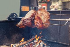 A spit for cooking roast shank in Prague on a Sunny day. A big piece of meat. National cuisine. The street food. The horizontal frame Royalty Free Stock Images