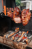 A spit for cooking roast shank in Prague on a Sunny day. National cuisine. The street food. The vertical frame Stock Image
