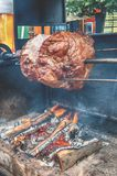 A spit for cooking roast shank in Prague on a Sunny day. National cuisine. The street food. The vertical frame royalty free stock photography