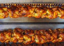 Spit-geroosterde rotisserie kippen onder gasvlam Stock Fotografie