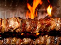 Spit roast with meat cooked on a spit in the fireplace 1. Spit roast with of tasty meat cooked on a spit in the fireplace 1 Royalty Free Stock Photo