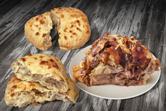 Spit Roasted Juicy Pork Ham With Two Pitta Bread Torn Loaves In Half Set On Old Cracked Flaky Wooden Garden Table Royalty Free Stock Image