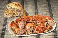 Spit Roasted Pork Shoulder Slices And Leavened Pitta Flatbread Torn Loaf Set On Plaited Ocher Paper Parchment Place Mat. Plateful Of Freshly Spit Roasted Pork royalty free stock image