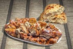 Spit Roasted Pork Shoulder Slices And Leavened Pitta Flatbread Torn Loaf Set On Plaited Ocher Paper Parchment Place Mat. Plateful Of Freshly Spit Roasted Pork stock photo