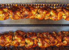 Spit-roasted rotisserie chickens under gas flame. Chickens roasting on spit under gas flame in Mexico Stock Photography