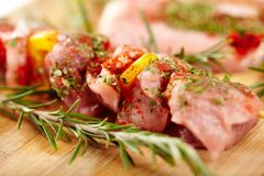 Spit of spiced raw pork meat with pepper on a wooden board Stock Photos