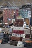 Spitalfields pajasmarknad Sale av gamla resväskor som ligger på de Välfylld galande på en ställning i bakgrunden av gammalt tyg Arkivfoton