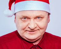Spiteful man in Santa Claus hat. Close up portrait of evil aged man in Santa Claus hat and red shirt over white background Royalty Free Stock Images