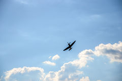 Spitfire on blue cloudy sky Royalty Free Stock Images