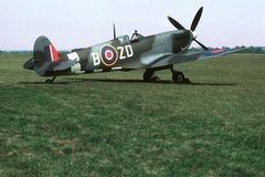 Spitfire Parked on Grass. British mark IX Spitfire parked beside a grass runway stock image