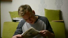 Spitting τσάι επάνω στο έγγραφο διαβάζοντας τις πλαστές ειδήσεις από το νεαρό άνδρα στο εσωτερικό φιλμ μικρού μήκους