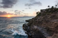 Spitting Caves in Oahu, Hawaii at sunset. With waves crashing up against the cliff and homes and palm trees on top of the cliff Royalty Free Stock Photography