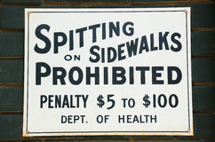 Spitting prohibited. Spitting on Sidewalks prohibited sign on a brick wall Royalty Free Stock Photo