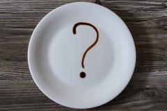 Spitze über Unkostenabschluß herauf Ansichtfoto der weißen Plattentonware auf Holztisch Eine Platte mit Fragezeichen auf ihm, ges stockbilder
