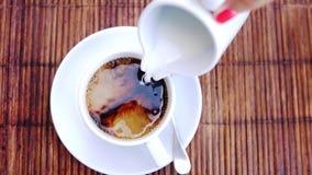 Spitze der Ansicht der auslaufenden Strommilch in eine Schale Espresso, Zeitlupe 1920x1080 stock footage