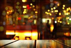 Spitze der hölzernen Tabelle mit Unschärfe bokeh Licht mit Schatten von Leuten herein stockbilder