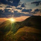 Spitze der Hügel- und Sonnenuntergangstrahlen Stockfoto